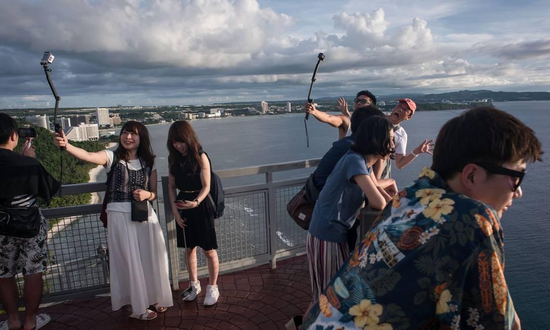 Essas turistas no Two Lovers Viewpoint, famoso mirante em Guam, não parecem muito preocupados com as tensões entre EUA e Coréia do Norte Foto: Ed Jones / AFP