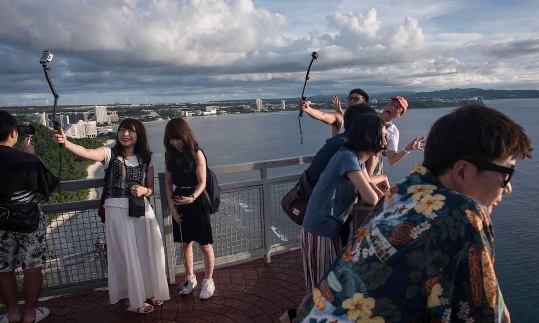 Essas turistas no Two Lovers Viewpoint, famoso mirante em Guam, não parecem muito preocupados com as tensões entre EUA e Coréia do Norte Ed Jones / AFP