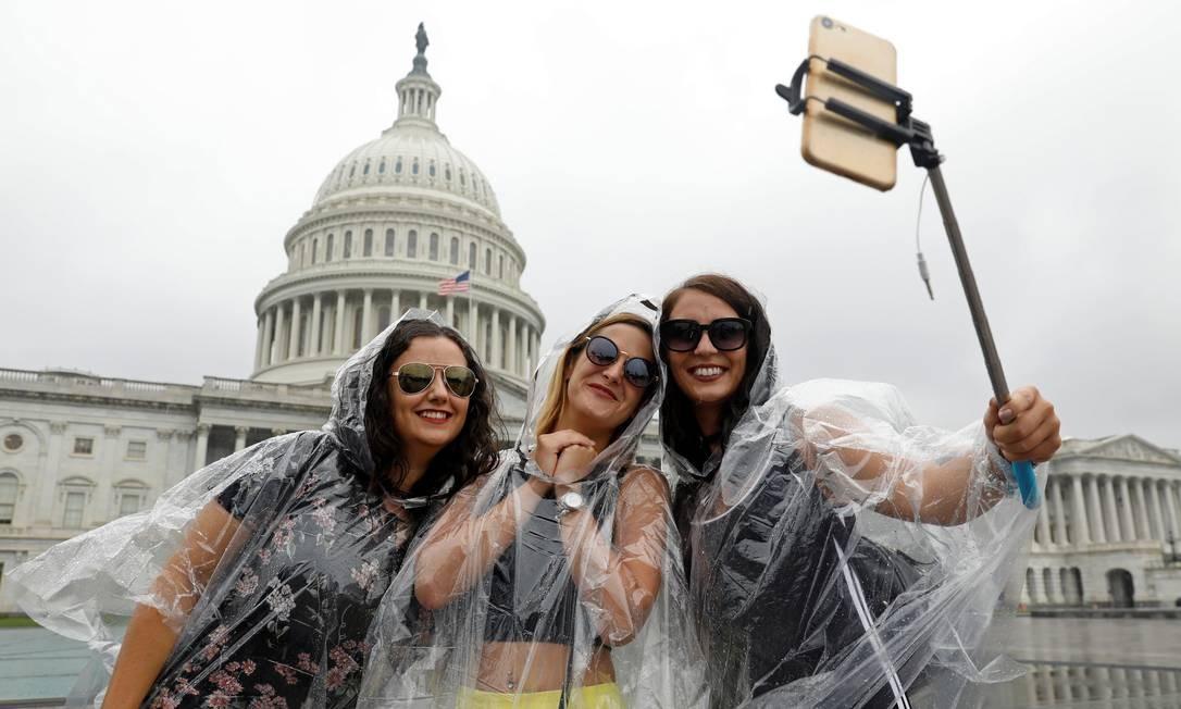 Nem a chuva desanima essas turistas em frente ao Capitólio dos EUA, em Washington DC Foto: Kevin Lamarque / REUTERS