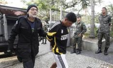 Um dos presos durante megaoperação chega à Divisao de Homicídios de Niterói Foto: Pedro Teixeira / Agência O Globo