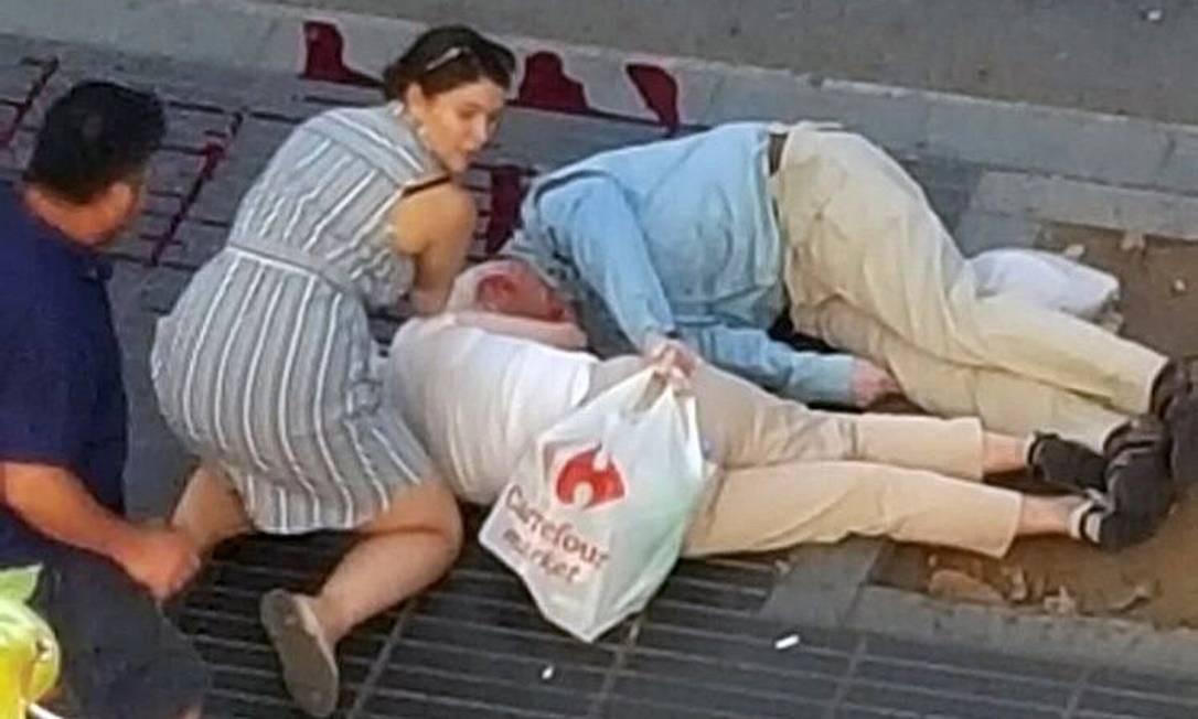Pessoas ajudam feridos no local do atentado em Barcelona Foto: STRINGER / REUTERS