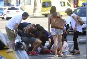 Pessoas ajudam ferido após atentado terrorista em Barcelona nesta quinta-feira Foto: Oriol Duran / AP