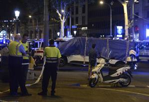 A van que atropelou uma multidão, deixando ao menos 13 mortos e ferindo outros 100, é retirada da avenida La Rambla, em Barcelona Foto: JOSEP LAGO / AFP