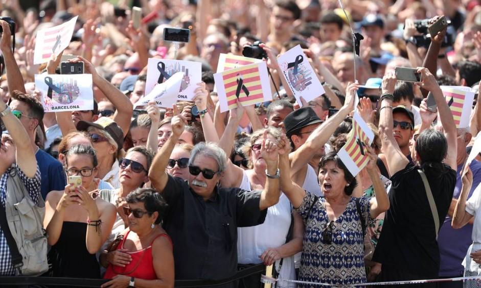 Pessoas seguram cartazes durante tributo na Praça da Catalunha, um dia após o atropelamento nas Ramblas que deixou 14 mortos e mais de 100 feridos em Barcelona, na Espanha Foto: SERGIO PEREZ / REUTERS