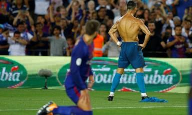Piqué, do Barça, observa Cristiano Ronaldo, do Real, comemorar um gol na Supercopa Foto: JUAN MEDINA / REUTERS
