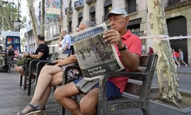 """Um senhor lê o jornal catalão """"el Periódico"""", na manhã desta sexta-feira, em La Rambla, mesma avenida em que um furgão atropelou dezenas de pessoas deixando 13 mortos nesta quinta-feira em Barcelona Foto: JAVIER SORIANO / AFP"""