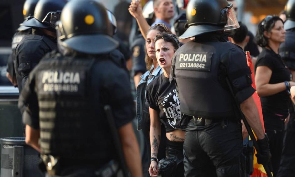 """Membros do grupo de ultradireita Falange enfrentam manifestantes anti-extrema-direita em manifestação, nesta sexta-feira, em La Rambla, avenida onde um atentado terrorista matou 13 pessoas e feriu mais de cem no dia anterior. Na manifestação, algumas pessoas gritavam a frase """"A Catalunha é cristã e não muçulmana!"""" Foto: JOSEP LAGO / AFP"""