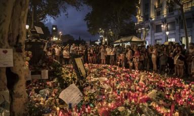 Pessoas se reúnem em um memorial às vítimas do ataque. Flores, mensagens e velas foram deixadas nas Ramblas Foto: Santi Palacios / AP