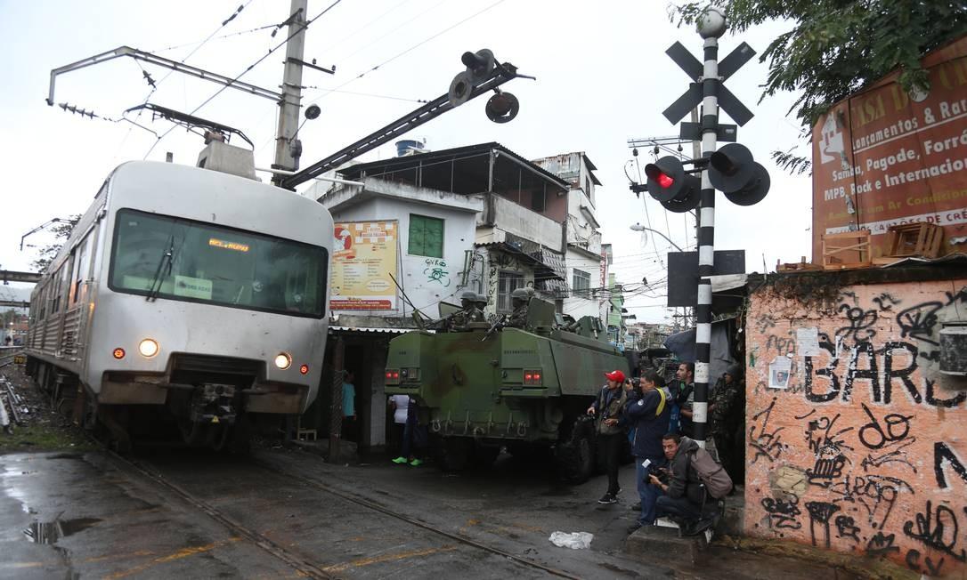 Composição da SuperVia passa próximo à blindado da Marinha na Favela do Jacarezinho Foto: Fabiano Rocha / Agência O Globo