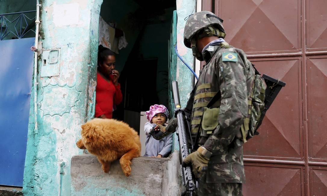 Em Manguinhos, criança aperta a mão de homem do Exército durante megaoperação das Forças de Segurança Foto: Pablo Jacob / Agência O Globo
