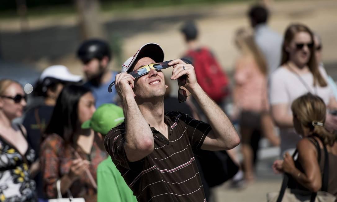 Do lado de fora do Museu Smithsonian do Espaço e do Ar, em Washington, um homem experimenta óculos para observação do eclipse solar Foto: BRENDAN SMIALOWSKI / AFP