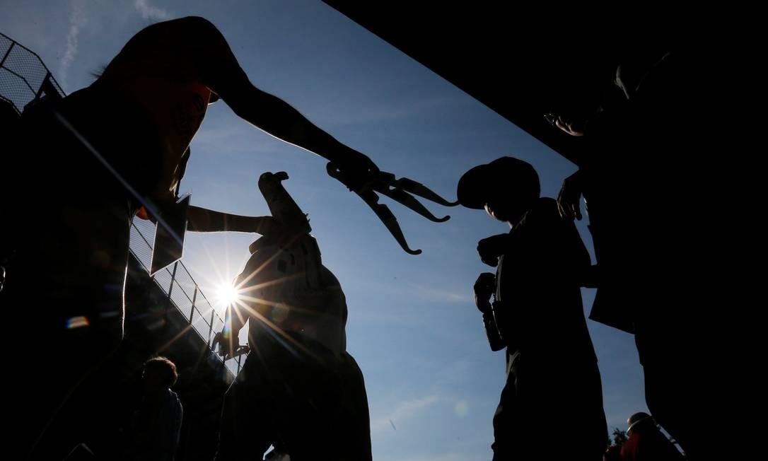 Pessoas distribuem óculos especiais para acompanhar o eclipse a quem foi nesta segunda-feira ao estádio de futebol da Universidade de Southern Illinois Foto: BRIAN SNYDER / REUTERS
