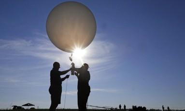 Nesta segunda-feira, o professor de química atmosférica Mike Newchurch, à esquerda, e sua aluna de graduação Paula Tucker, da Universidade do Alabama, preparam um balão para ser solto durante o ápice do eclipse solar total Foto: Mark Humphrey / AP