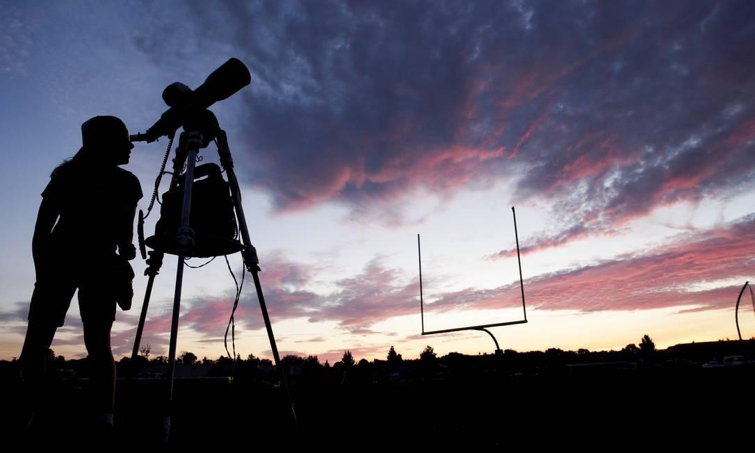 Poucos minutos após o amanhecer desta segunda-feira, uma mulher olhava por um telescópio no Oregon, nos EUA, preparando-se para o eclipse total mais tarde Foto: JASON REDMOND / REUTERS