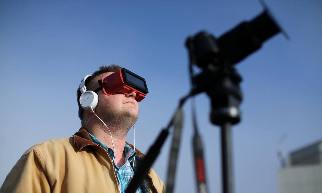 James Courtwright fez ajustes na câmera e comprou um óculos especial para acompanhar o raro fenômeno Foto: MIKE BLAKE / REUTERS