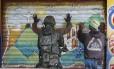 Um militar revista moradores do Jacarezinho: integrantes das Forças Armadas e policiais tomaram oito comunidades da Zona Norte da cidade, nas quais foram apreendidas nove pistolas, uma espingarda e um revólver Foto: Domingos Peixoto / Agência O Globo