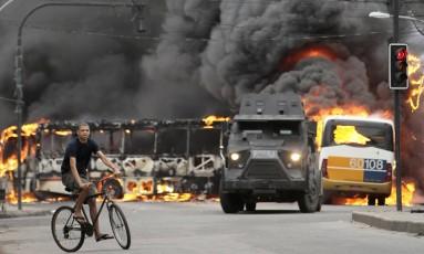 Rapaz passa por ônibus incendiados após guerra entre traficantes no Rio Foto: Ricardo Moraes / Reuters