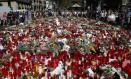 Pessoas reúnem velas e flores no chão em homenagem às vítimas do ataque terroristas que deixou 15 mortos e 130 feridos na Catalunha, Espanha Foto: Manu Fernandez / AP