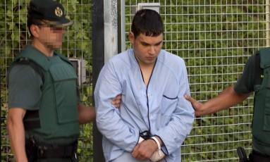 Mohamed Houli Chemlal, suspeito de envolvimento na célula terrorista que realizou dois ataques na Espanha, é escoltado pela polícia até audiência em Madri Foto: STRINGER / AFP