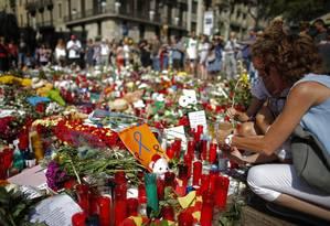 Mulheres deixam velas e flores em Barcelona, após um ataque terrorista que deixou 15 mortos e 130 feridos Foto: Manu Fernandez / AP