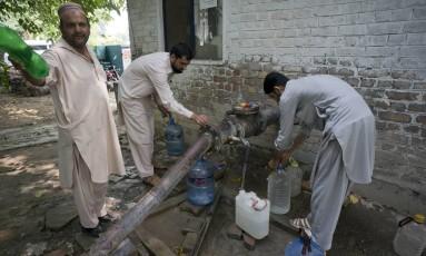 Homens coletam água de um poço em Islamabad, no Paquistão Foto: B.K. Bangash / AP