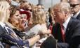 Plateia segura. Trump segura uma criança entregue por uma apoiadora ao chegar para um evento com veteranos das Forças Armadas em Reno, Nevada: vaivém emocional