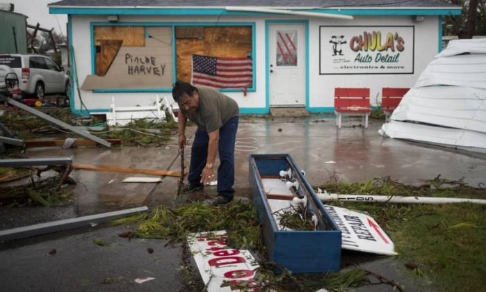 Dono de um estabelecimento comercial, Carlos Lopez limpa os danos deixados por ventos e chuva na frente da sua loja; autoridades alertam população a tomar medidas de precaução Foto: ADREES LATIF / REUTERS