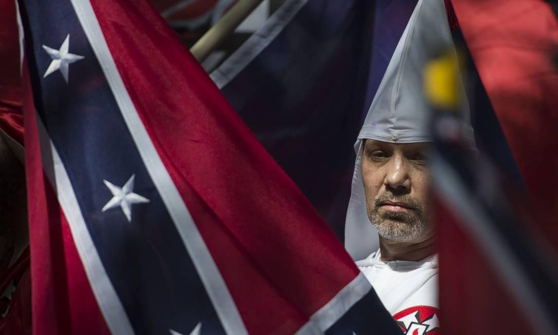 Ku Klux Klan. Em julho, membro do grupo defende proteção a monumentos de homenagem a confederados em Charlottesville; cidade do estado da Viginia foi cenário de confrontos entre extremistas e manifestante antirracismo Foto: ANDREW CABALLERO-REYNOLDS / AFP