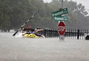Homens usam bote para fugir da inundação Foto: Mark Mulligan / AP
