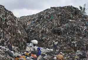Imagem mostra homens e mulheres escavando material reciclável entre montanhas de lixo em Nairóbi, no Quênia Foto: Ben Curtis / AP
