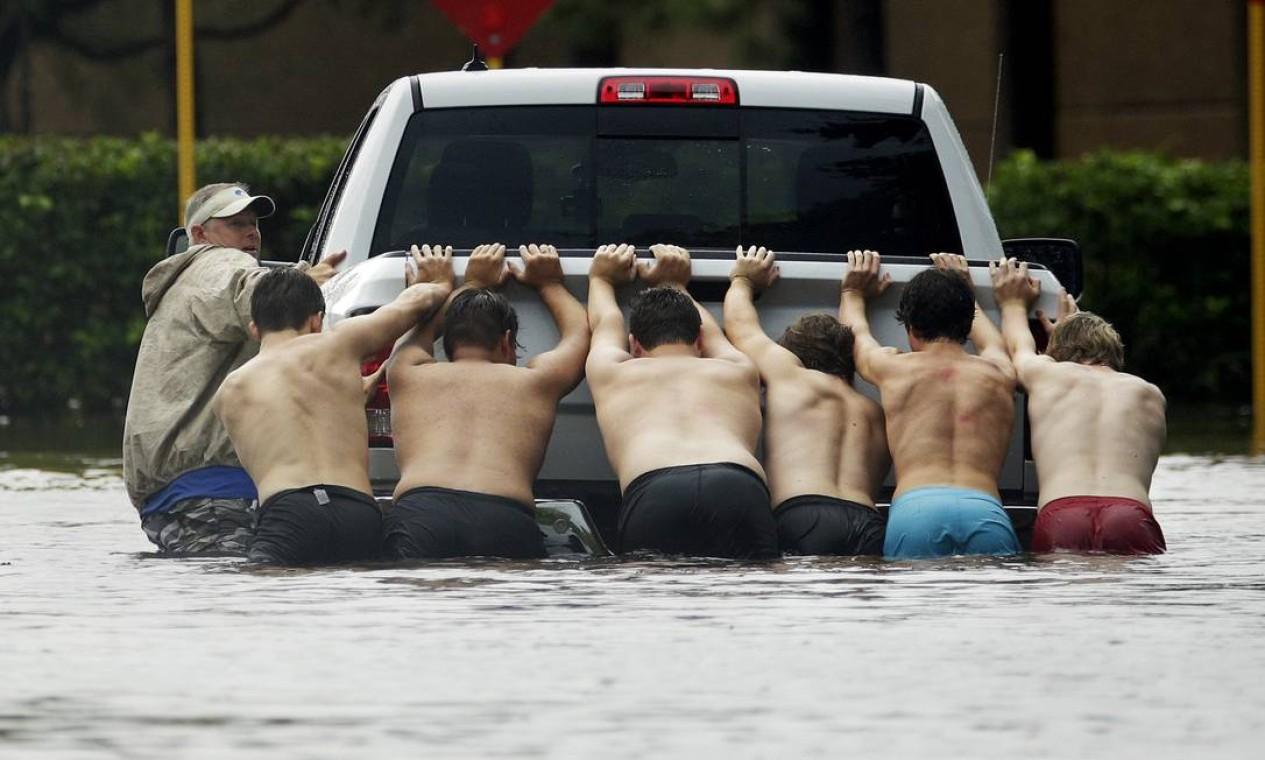 Moradores se unem para retirar veículo de uma rua alagada em Houston, no Texas. A cidade é uma das mais atingidas pela tempestade tropical Foto: Charlie Riedel / AP