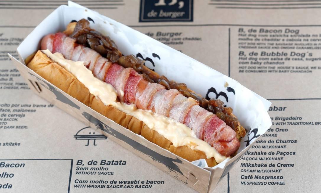 O Bacon Dog, do B de Burger, é um cachorro quente feito com salsicha enrolada no bacon frito, mix de queijos e cebola na cerveja escura (R$29). Foto: Divulgação / Fábio Rossi / Divulgação / Fábio Rossi