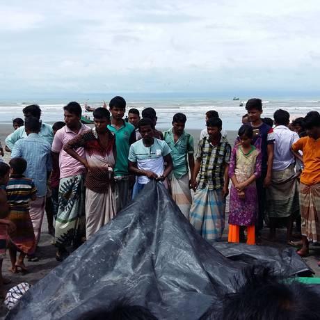 Pessoas assistem enquanto um homem cobre os corpos de mulheres e crianças rohingya que morreram afogados, após os barcos em que estavam naufragarem no rio Naf Foto: SUZAUDDIN RUBEL / AFP
