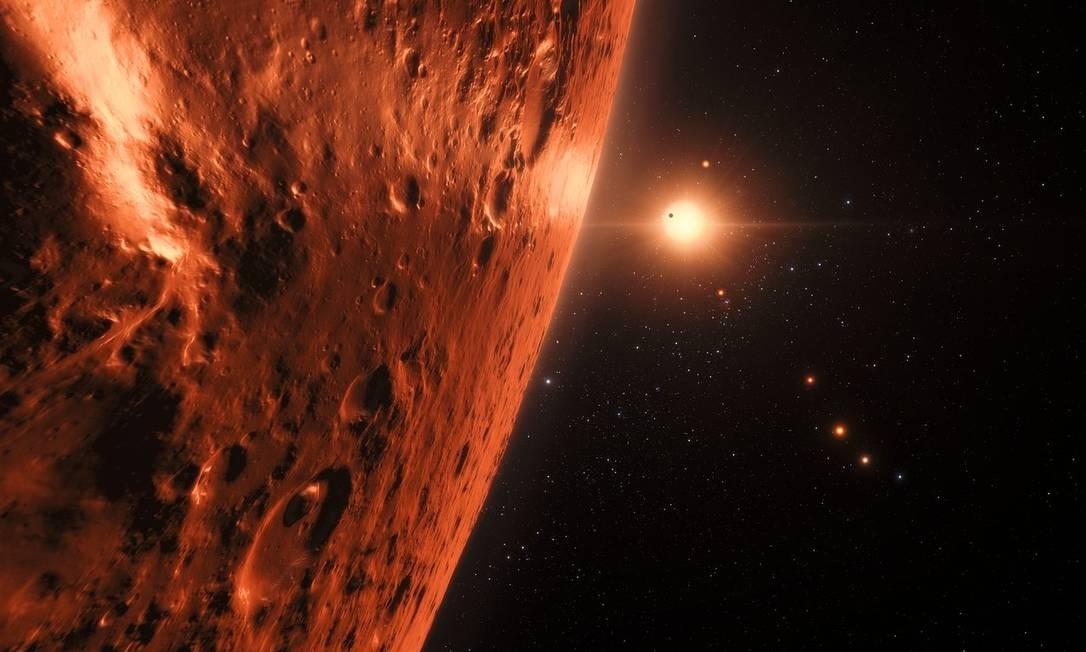 Ilustração mostra a possível superfície de um dos planetas do sistema Trappist-1 com a estrela e outros dos exoplanetas ao fundo: alguns deles ainda podem ter água em estado líquido, condição para desenvolvimento ou manutenção da vida como conhecemos Foto: ESO/N. Bartmann/spaceengine.org