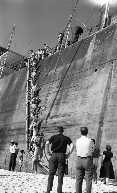 """08/06/1958 - """"O Camboinhas transformou-se em atração turística: uma escada colocada em seu costado permite o acesso dos visitantes, que são muitos e que ali vão levar as suas despedidas ao velho barco em agonia nas areias de Itaipú"""" Foto: Agência O Globo / Arquivo"""