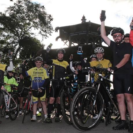 Ciclistas exibem na Vista Chinesa, no Parque Nacional da Tijuca, seus celulares, ferramentas de mobilização contra a insegurança no local Foto: Julio Cesar Guimaraes / Agência O Globo