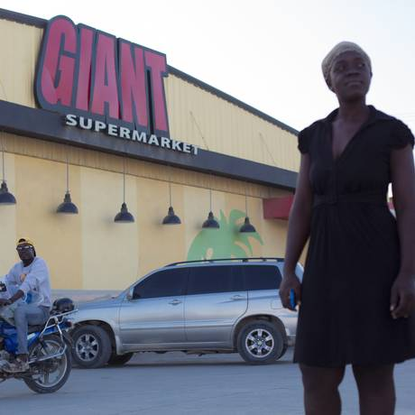 Em crescimento. Um homem carrega as compras da amiga em um dos supermercados da rede Giant, no Centro Comercial Plaza 22, em Porto Príncipe: 3 unidades novas em seis anos Foto: Daniel Marenco / Agência O Globo