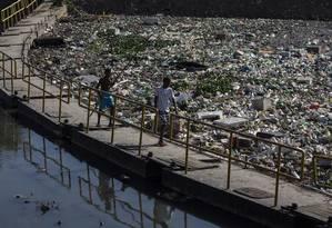 Meninos da Cidade de Deus caminham sobre barreira na Unidade de Tratamento de Rio do Arroio Pavuna: contenção impede que avalanche de resíduos chegue a lagoas da Barra. Jovens catam bolas em meio ao lixo Foto: Agência O Globo / Alexandre Cassiano