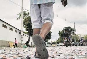 Eleitor caminha próximo ao local de votação no complexo de favelas da Maré, em meio à sujeira da propaganda política Foto: Daniel Marenco / Agência O Globo