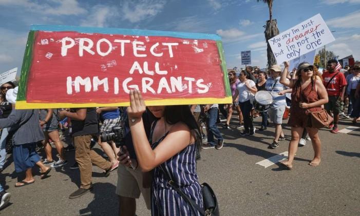 Apoiadores do Daca entoam slogans e carregam cartazes durante um protesto no dia do trabalho em Los Angeles, EUA Foto: Richard Vogel / AP