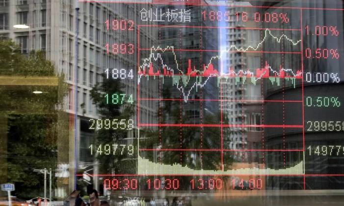Janela de uma casa de corretora mostra índice de negociação de ações em Pequim, China Foto: Andy Wong / AP