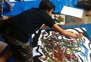Pintura. Um dos adolescentes em ação: o Jacarezinho para o asfalto ver Foto: Divulgação