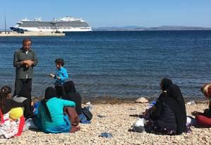 Refugiados se reúnem na praia de Chios, enquanto um navio de cruzeiro chega com turistas: : fim do verão coincide com o aumento de chegada de imigrantes, que aproveitam o relaxamento na patrulha na costa turca Foto: Lucila Runnacles