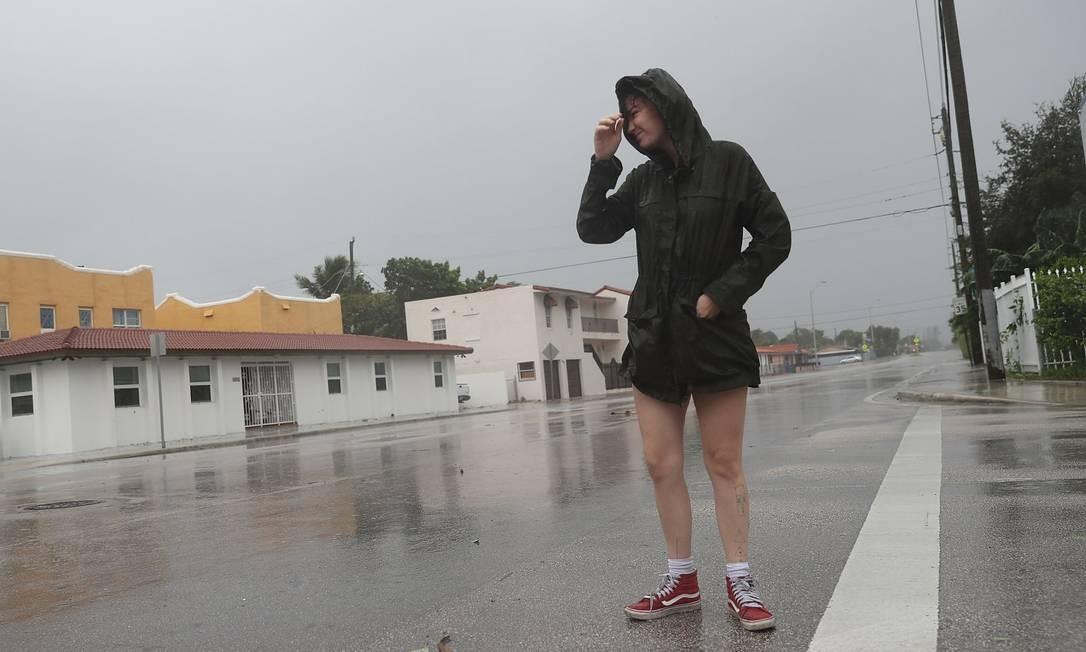 A moradora de Miami Jonvi Delsol checa a situação na rua enquanto os ventos ainda não atingem os níveis máximos esperados Foto: JOE RAEDLE / AFP