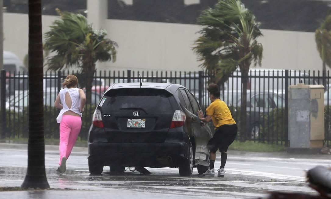 Mulheres tentam entrar no carro em Hialeah Foto: Alan Diaz / AP