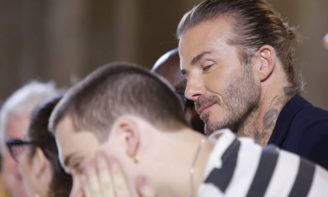 Será que David Beckham estaria tentando espiar o celular de Brooklyn? EDUARDO MUNOZ ALVAREZ / AFP