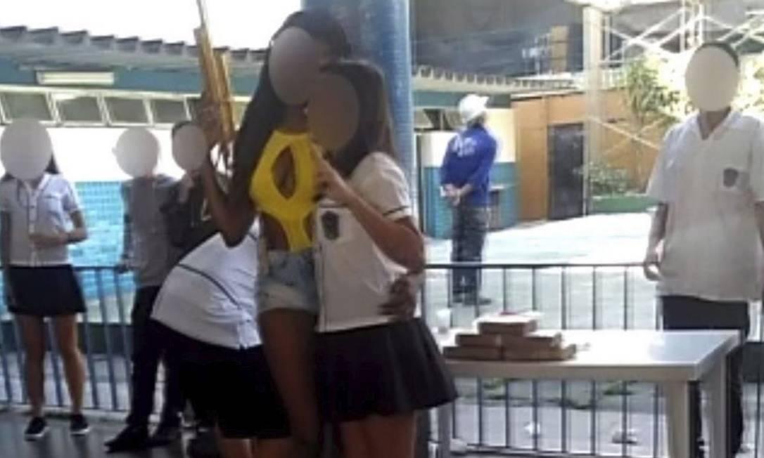 Caracterização. Uma aluna posa para foto usando short e maiô e segurando uma réplica de arma Foto: Reprodução da internet