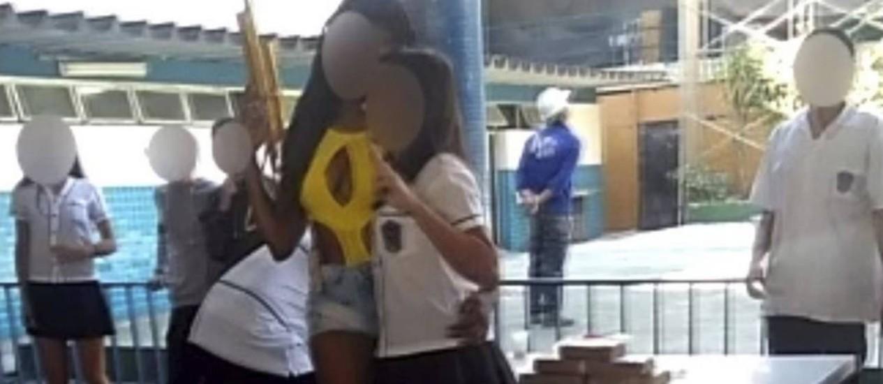 Uma aluna posa para foto usando short e maiô e segurando uma réplica de arma Foto: Reprodução da Internet