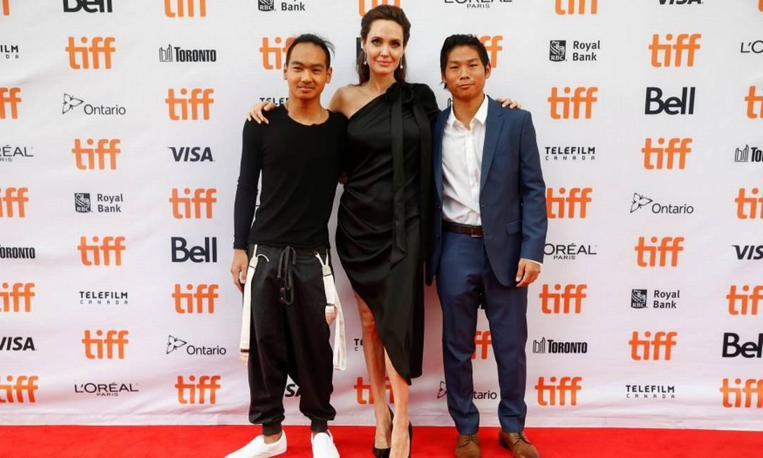 Angelina Jolie, que é diretora e roteirista do longa, posa com os filhos Maddox (à esquerda) e Pax (à direita). Maddox é produtor-executivo do filme e nasceu no Camboja, onde se passa a história. Pax também ajudou no longa e é do Vietnã MARK BLINCH / REUTERS