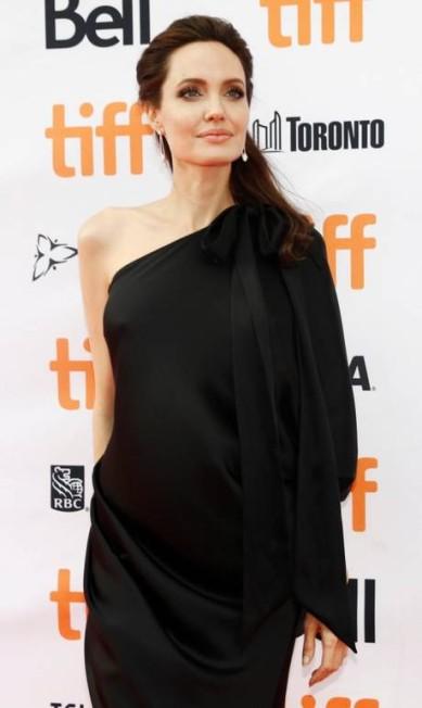 Angelina Jolie disse ter se interessado pela história por causa de Maddox. O longa mostra uma jovem, que viveu o o genocídio da década de 1970, no Camboja, e é forçada a trabalhar no campo, antes de virar uma criança soldado MARK BLINCH / REUTERS